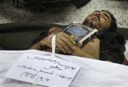 Islam&#39;s holy book, the Quran, is placed on the body of Yemeni anti-government protestor, Abdou Saeed Mohammed, who was killed during recent clashes with security at a field hospital in Sanaa, Yemen, Tuesday, Sept. 20, 2011. Rapidly escalating street battles between opponents of Yemen&#39;s regime and forces loyal to its embattled president spread to the home districts of senior government figures and other highly sensitive areas of the capital on Tuesday. A third day of fighting, including a mortar attack on unarmed protesters, killed nine people, medical officials said. Writing in Arabic reads: Martyr  Abdou Saeed Mohammed, Taiz&#34;.&#40;AP Photo&#47;Hani Mohammed&#41; <span class=meta>(AP Photo&#47; Hani Mohammed)</span>