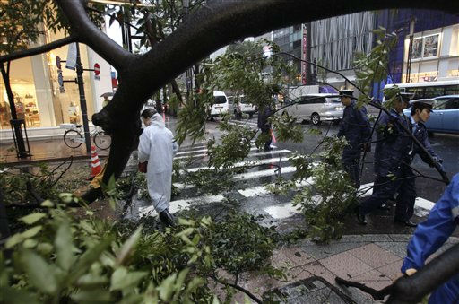 Policemen attempt to remove a tree toppled by strong wind due to Typhoon Roke at Ginza shopping district in Tokyo, Japan,  Wednesday, Sept. 21, 2011.  The storm, packing sustained winds of up to 100 mph &#40;162 kph&#41;, made landfall in the afternoon near the central Japanese city of Hamamatsu, about 125 miles &#40;200 kilometers&#41; west of Tokyo. The storm was expected to cut a path northeast through the capital and into the northeastern region of Tohoku, which was devastated by the March 11 tsunami and earthquake.  &#40;AP Photo&#47;Shizuo Kambayashi&#41; <span class=meta>(AP Photo&#47; Shizuo Kambayashi)</span>