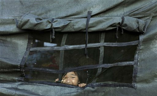 "<div class=""meta ""><span class=""caption-text "">An Indian child, a survivor of last Sunday's 6.9-magnitude earthquake, looks out from the window of a tent where she took shelter in Chungthang, India, Thursday, Sept. 22, 2011. Rescuers in helicopters on Thursday reached some of the villages in India's remote northeast that were cut off by the powerful earthquake that rattled the Himalayan region last weekend. (AP Photo/Altaf Qadri) (AP Photo/ Altaf Qadri)</span></div>"