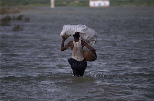 A displaced Pakistani man wades through flood water, carrying belongings in Tando Muhammad Khan near Hyderabad, Pakistan, Thursday, Sept. 22, 2011. In Pakistan&#39;s Sindh province alone, the floods have killed over 220 people, damaged or destroyed some 665,000 homes and displaced more than 1.8 million people, according to the United Nations. Neighboring Baluchistan province has also been affected. &#40;AP Photo&#47;Muhammed Muheisen&#41; <span class=meta>(AP Photo&#47; Muhammed Muheisen)</span>