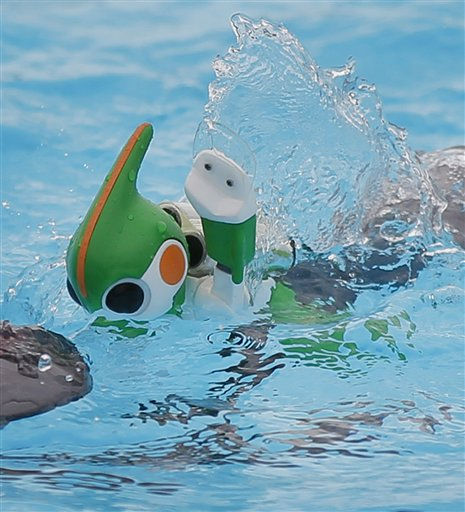 EDITORS NOTE: THIS IS A RECROPPED VERSION OF XITS101 - Robot Evolta swims during a family triathlon event in Oiso, west of Tokyo, Friday, Sept. 23, 2011. Three types of the 17 centimeter &#40;6.7 inch&#41; -tall, green and white imp-like robot, powered by three of Panasonic&#39;s rechargeable Evolta AA batteries, plan to challenge an ultra distance triathlon on the Island of Hawaii on Oct. 24, covering the 3.8-kilometer &#40;2.4-mile&#41; swimming, 180-km &#40;112-mile&#41; bicycling and 42.2-km &#40;26-mile&#41; running, in one week with only three rechargeable batteries. A black keel-like floater will be attached to assit the robot to swim in high waves and fast tides during the open water swimming. &#40;AP Photo&#47;Itsuo Inouye&#41; <span class=meta>(AP Photo&#47; Itsuo Inouye)</span>