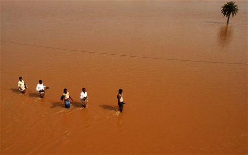 "<div class=""meta ""><span class=""caption-text "">In this photo taken on Sunday, Sept. 25, 2011, Indian villagers carrying relief materials walk through flood waters at Rasulpur village in Orissa's Jajpur district, India. India's monsoon season, which runs from June through September, brings rains that are vital to agriculture but also cause floods and landslides. (AP Photo/Biswaranjan Rout) (AP Photo/ Biswaranjan Rout)</span></div>"