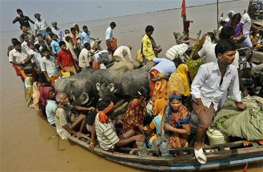 Indian villagers with their cattle cross flood waters on a boat at Kasimpurchak near Danapur Diara in Patna, India, Tuesday, Sept. 27, 2011. Monsoon rains destroyed mud huts and flooded wide swaths of northern and eastern India in recent days, leaving hundreds of thousands marooned by raging waters, officials said Monday. &#40;AP Photo&#47; Aftab Alam Siddiqui&#41; <span class=meta>(AP Photo&#47; Aftab Alam Siddiqui)</span>