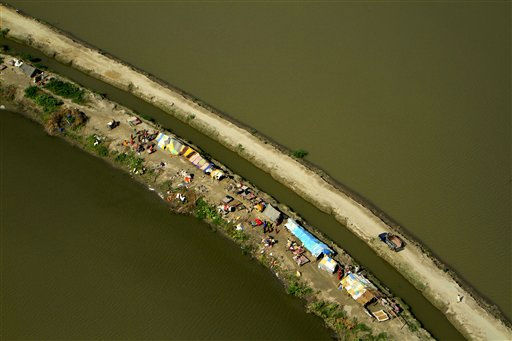 "<div class=""meta ""><span class=""caption-text "">In this photo taken from a Army helicopter, displaced Pakistanis take refugee along a road surrounded by flood water, after fleeing their flood-hit homes in Kunri, in Umerkot District of Pakistan's Sindh province, Tuesday, Sept. 27, 2011. In Pakistan's Sindh province alone, the floods have killed over 200 people, damaged or destroyed some 665,000 homes and displaced more than 1.8 million people, according to the United Nations. Neighboring Baluchistan province has also been affected. (AP Photo/Shakil Adil) (AP Photo/ Shakil Adil)</span></div>"