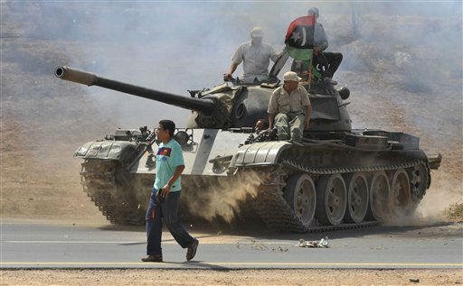 Libyan revolutionary fighters ride on a tank as they gathering on the main road outside Sirte, Libya, Wednesday, Sept. 28, 2011. Thousands of revolutionary fighters wait around Sirte to enter the home town of Libya&#39;s ousted leader Moammar Gadhafi. &#40;AP Photo&#47;Bela Szandelszky&#41; <span class=meta>(AP Photo&#47; Bela Szandelszky)</span>