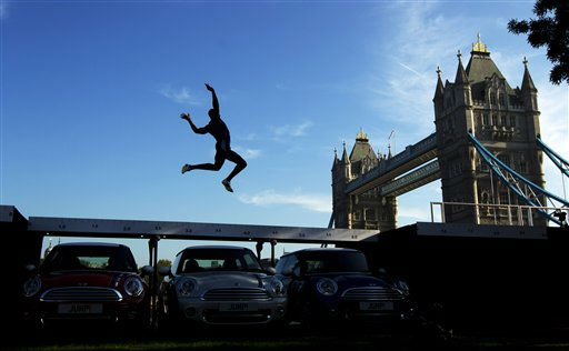 Current British long jump champion J.J. Jegede is silhouetted as he performs an exhibition jump over three Mini cars backdropped by Tower Bridge in London, Wednesday, Sept. 28, 2011. The event took place Wednesday to mark the launch of the Mini London 2012 edition models, of which 2,012 will be produced ahead of the London 2012 Olympic Games. &#40;AP Photo&#47;Matt Dunham&#41; <span class=meta>(AP Photo&#47; Matt Dunham)</span>