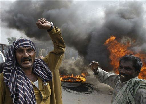 "<div class=""meta ""><span class=""caption-text "">Displaced flood-affected villagers burn tires and block the highway demanding relief from the Pakistan government in Umerkot , Pakistan on Wednesday, Sept. 28, 2011. The flood have killed over 220 people and destroyed some 665,000 homes displacing 1.8 million people in Sindh province. (AP Photo/Shakil Adil) (AP Photo/ Shakil Adil)</span></div>"