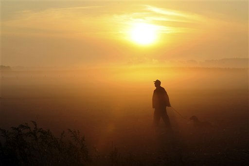 "<div class=""meta ""><span class=""caption-text "">Jan Thoolen walks his dog as the sun shines through early morning mist near Slek, southeast Netherlands, Thursday, Sept. 29, 2011. The Netherlands is enjoying unseasonably warm weather for this time of the year. (AP Photo/Ermindo Armino) (AP Photo/ Ermindo Armino)</span></div>"