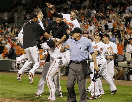Members of the Baltimore Orioles surround teammate Nolan Reimold &#40;14&#41; after he scored the winning run in the ninth inning of a baseball game against the Boston Red Sox on Wednesday, Sept. 28, 2011, in Baltimore. Baltimore won 4-3, and Boston was eliminated from the playoffs after the Tampa Bay Rays beat the New York Yankees in extra innings minutes after Boston&#39;s loss. &#40;AP Photo&#47;Patrick Semansky&#41; <span class=meta>(AP Photo&#47; Patrick Semansky)</span>