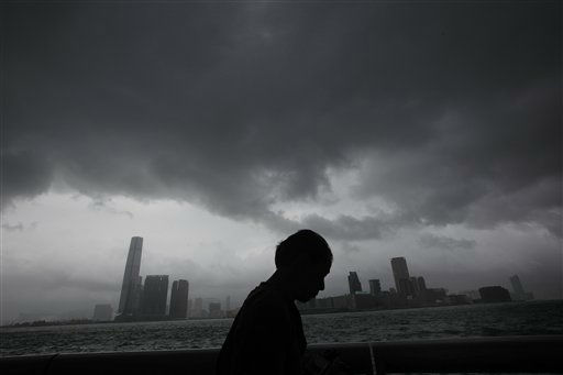 A man walks at a pier against a backdrop of Hong Kong&#39;s Victoria Habour Thursday, Sept. 29, 2011. Residents of Hong Kong hunkered down Thursday as they rode out a powerful typhoon that brought death and destruction when it tore through the Philippines earlier this week. Hong Kong&#39;s stock market suspended trading and shops and businesses shuttered as Typhoon Nesat made its way across the South China Sea from the Philippines, where the storm killed 35 people and that left another 45 missing. &#40;AP Photo&#47;Vincent Yu&#41; <span class=meta>(AP Photo&#47; Vincent Yu)</span>