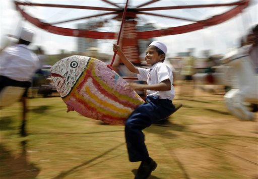 A Sri Lankan Muslim boy takes ride on a swing on World Children&#39;s Day in Colombo, Sri Lanka, Friday, Sept. 30, 2011. &#40;AP Photo&#47;Eranga Jayawardena&#41; <span class=meta>(AP Photo&#47; Eranga Jayawardena)</span>