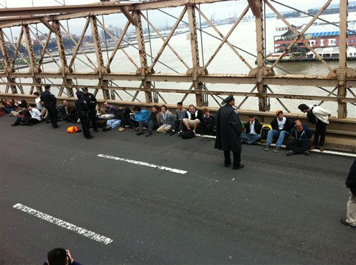 Police contain arrested Wall Street movement protesters on the Brooklyn Bridge in New York, Saturday, Oct. 1, 2011. More than 700 protesters demonstrating against corporate greed, global warming and social inequality, among other grievances, were arrested Saturday after they swarmed the Brooklyn Bridge and shut down a lane of traffic for several hours in a tense confrontation with police. &#40;AP Photo&#47;Rose Bookbinder&#41; <span class=meta>(AP Photo&#47; Rose Bookbinder)</span>