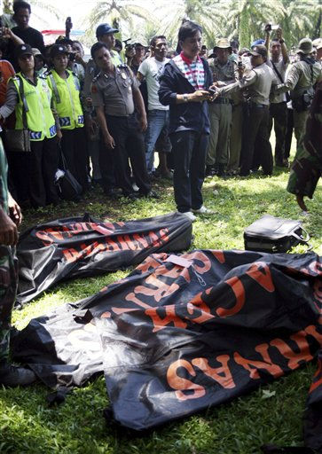 Indonesian police check the bodies of plane crash victims, after the rescue team brought the body from jungle,  in Bahorok,  North  Sumatra, Indonesia, Sunday, Oct. 2, 2011. The bodies of all 18 people who were on board a plane that crashed into the jungle-covered mountains of western Indonesia were recovered from the wreckage Saturday, an official said.&#40;AP Photo&#47;Binsar Bakkara&#41; <span class=meta>(AP Photo&#47; Binsar Bakkara)</span>