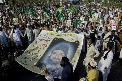 "<div class=""meta ""><span class=""caption-text "">Supporters of the religious group Sunni Tehreek hold a huge poster of Mumtaz Qadri, the confessed killer of a liberal Pakistani governor, with wording 'Qadri, we salute your courage,' during a rally to condemn a court decision against Qadri, Sunday, Oct. 2, 2011 in Karachi, Pakistan. A Pakistani court convicted and sentenced Qadri to death for the killing of a liberal governor earlier this year, a murder that led to fears the country was buckling under the weight of extremism. (AP Photo/Fareed Khan) (AP Photo/ Fareed Khan)</span></div>"