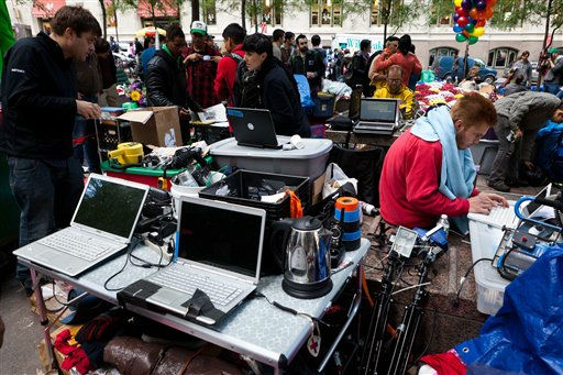Protestors at Occupy Wall Street&#39;s media area coordinate news updates on laptop computers powered by a portable gas-powered generator in Manhattan&#39;s financial district&#39;s Zuccotti park, Sunday, Oct. 2, 2011, in New York. The Occupy Wall Street demonstration started out small, with less than a dozen college students, but has grown to include thousands of people in communities across the country. &#40;AP Photo&#47;John Minchillo&#41; <span class=meta>(AP Photo&#47; John Minchillo)</span>