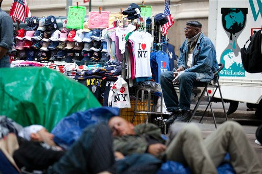 A street vendor waits for customers alongside lounging Occupy Wall Street protestors in Zuccotti park Sunday, Oct. 2, 2011, in New York. The ongoing protests have gathered momentum and gained participants in recent days as news of mass arrests and a coordinated media campaign by the protestors have given rise to similar demonstrations around the country. &#40;AP Photo&#47;John Minchillo&#41; <span class=meta>(AP Photo&#47; John Minchillo)</span>