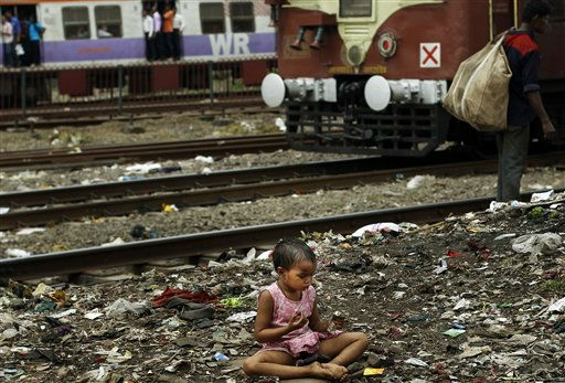 A girl brushes her teeth near railway tracks in Mumbai, India, Monday, Oct. 3, 2011. Last month, India?s Planning Commission, which helps set economic policy, told the Supreme Court that the poverty line for the nation?s cities was 1,920 rupees &#40;US39 dollars&#41; per person a month. This has angered activists who say the figure is ridiculously low. &#40;AP Photo&#47;Rafiq Maqbool&#41; <span class=meta>(AP Photo&#47; Rafiq Maqbool)</span>