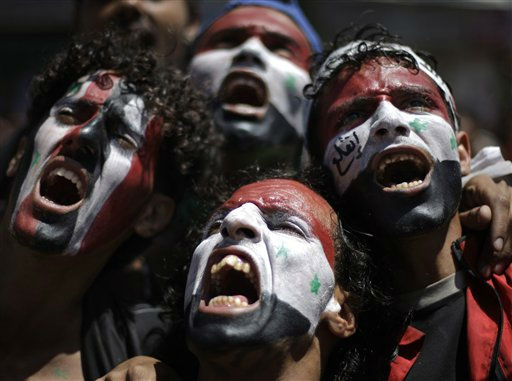 Protestors with Yemeni and Syrian flags painted on their faces chant slogans during a demonstration to demand the resignation of Yemen&#39;s President Ali Abdullah Saleh in Sanaa, Yemen, Monday, Oct. 3, 2011. The Arabic writing on the man&#39;s face at right reads &#34;get out.&#34; &#40;AP Photo&#47;Hani Mohammed&#41; <span class=meta>(AP Photo&#47; Hani Mohammed)</span>