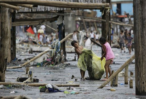 "<div class=""meta ""><span class=""caption-text "">Filipino children carry their playmate in a net at an area where most of the houses were wiped out by strong currents from recent typhoons along a coastal village in Tangos, Navotas city, north of Manila, Philippines on Monday Oct. 3, 2011. Floodwaters slowly receded Monday in many parts of the northern Philippines after two typhoons amid appeals for more boats to bring food and water to residents refusing to abandon inundated homes. (AP Photo/Aaron Favila) (AP Photo/ Aaron Favila)</span></div>"