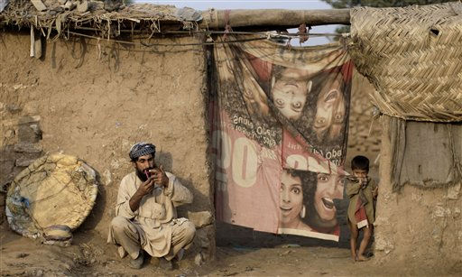 Matti Noor Khan, 35, combs his beard while sitting in front of his home, shortly before heading to a fruit market where he works, in a slum on the outskirts of Islamabad, Pakistan, Tuesday, Oct. 4, 2011. &#40;AP Photo&#47;Muhammed Muheisen&#41; <span class=meta>(AP Photo&#47; Muhammed Muheisen)</span>