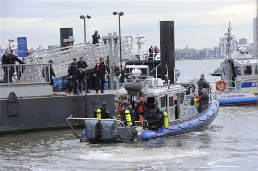 Divers prepare to enter the waters of the East River after a helicopter crashed, Tuesday, Oct. 4, 2011, in New York. A helicopter with five people aboard crashed into the East River on Tuesday afternoon after taking off from a launch pad on the riverbank, killing one and seriously injuring at least two others. &#40;AP Photo&#47; Louis Lanzano&#41; <span class=meta>(AP Photo&#47; Louis Lanzano)</span>