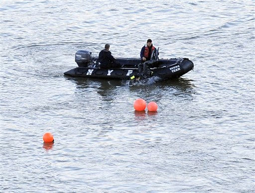 A diver enters the waters of the East River next to orange buoys that mark the spot where a helicopter crashed, Tuesday, Oct. 4, 2011, in New York. A Bell 206 helicopter with five people aboard crashed into the river after taking off from a launch pad on the riverbank, killing one passenger and injuring the others. &#40;AP Photo&#47;Louis Lanzano&#41; <span class=meta>(AP Photo&#47; Louis Lanzano)</span>