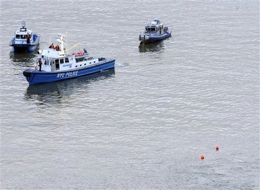 Police boats are on the scene where a helicopter crashed into the East River, marked by orange Buoys, Tuesday, Oct. 4, 2011, in New York. A Bell 206 helicopter with five people aboard crashed into the river after taking off from a launch pad on the riverbank, killing one passenger and injuring the others. &#40;AP Photo&#47;Louis Lanzano&#41; <span class=meta>(AP Photo&#47; Louis Lanzano)</span>