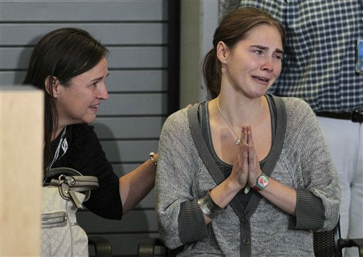 Amanda Knox motions to cheering supporters as her mother, Edda Mellas, looks on at a news conference shortly after her arrival at Seattle-Tacoma International Airport Tuesday, Oct. 4, 2011, in Seattle. It&#39;s been four years since the University of Washington student left for the study abroad program in Perugia and landed in prison. The group Friends of Amanda Knox and others have been awaiting her return since an Italian appeals court on Monday overturned her conviction of sexually assaulting and killing her British roommate, Meredith Kercher. &#40;AP Photo&#47;Elaine Thompson&#41; <span class=meta>(AP Photo&#47; Elaine Thompson)</span>