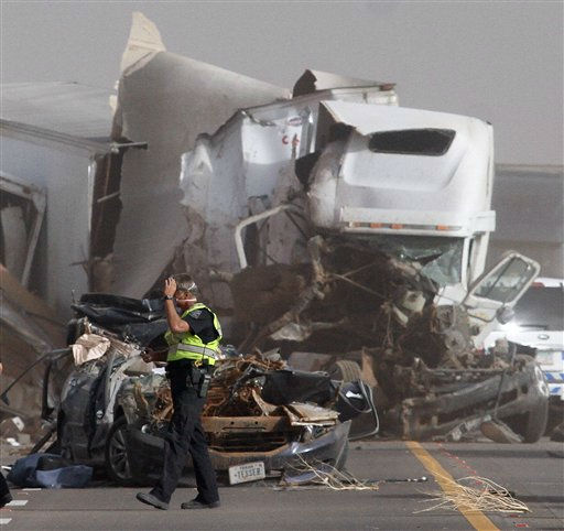 An Arizona Department of Public Safety Officer walks in front of two vehicles that were involved in two crashes that involved 16 vehicles on Interstate 10 near Picacho Peak, about midway between Phoenix and Tucson, Tuesday, Oct. 4, 2011. &#40;AP Photo&#47;Darryl Webb&#41; <span class=meta>(AP Photo&#47; Darryl Webb)</span>