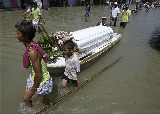 Residents pull a coffin on board a small boat as they wade along the flood-hit area of Calumpit, Bulacan province, north of Manila, on Wednesday Oct. 5, 2011. Flooding from back to back typhoons have affected more than half a million people in northern Philippines. The body inside the coffin did not die because of  the floods. &#40;AP Photo&#47;Aaron Favila&#41; <span class=meta>(AP Photo&#47; Aaron Favila)</span>