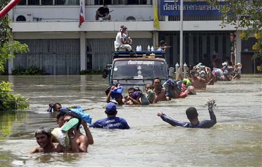 Prisoners at Ayutthaya prison wade in line in a chest-deep flood water to board a bus during an evacuation after flood water hit Ayutthaya province, central Thailand Thursday, Oct. 6, 2011. Nearly 5,000 prisoners in this province were evacuated to the prisons in nearby provinces of Nonthaburi and Lopburi. Flooding in Ayutthaya, the old Thai capital, could threaten ancient Buddhist temples and have alerted residents there to be ready to evacuate as a tropical storm approaches the region. &#40;AP Photo&#41; <span class=meta>(AP Photo&#47; Anonymous)</span>