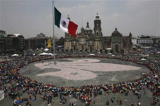 Hundreds gather to watch as boy scouts put the finishing touches on a gigantic fleur-de-lis they formed using an estimated 642,066 recycled aluminum cans at the Zocalo Plaza in Mexico City, Sunday Oct. 9, 2011. Thousands of Mexican boys scouts descend on the main plaza for the annual event to form their group&#39;s emblem. According to organizers the cans used to make the giant emblem are sold and the money used to help the needy. &#40;AP Photo&#47;Marco Ugarte&#41; <span class=meta>(AP Photo&#47; Marco Ugarte)</span>