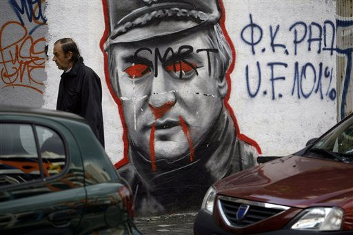 In this photo taken on Monday, Oct. 10, 2011, a man passes by a defaced mural depicting former war crimes fugitive Ratko Mladic in Belgrade, Serbia. When Serbia arrested Mladic earlier this year, its rocky road leading to European Union membership appeared finally clear of the key obstacle. But then came riots by Serbs in Kosovo, including clashes with NATO-led peacekeepers, and German Chancellor Angela Merkel&#39;s demand that Serbia must abandon its claim over the former province before finally becoming a EU candidate. The letters on the mural read &#34;Death&#34; in Serbian. &#40;AP Photo&#47; Marko Drobnjakovic&#41; <span class=meta>(AP Photo&#47; Marko Drobnjakovic)</span>