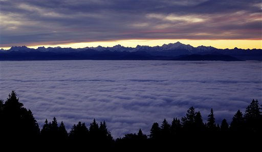 The Alps mountain range, including the Mont Blanc, right, western Europe&#39;s highest peak at 4,810 meters &#40;15,780 feet&#41; are sandwiched between clouds, as dawn breaks in La Barillette, 37 kilometers &#40;23 miles&#41; east of Geneva, Switzerland, Tuesday, Oct. 11, 2011. &#40;AP Photo&#47;David Azia&#41; <span class=meta>(AP Photo&#47; David Azia)</span>