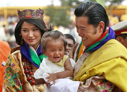 King Jigme Khesar Namgyal Wangchuck, right, holds a young child as he greets locals with Queen Jetsun Pema during a celebration after they were married at the Punakha Dzong in Punakha, Bhutan, Thursday, Oct. 13, 2011. The 31-year-old reformist monarch of the small Himalayan Kingdom wed his commoner bride in a series ceremonies Thursday in the 17th century monastic fortress. &#40;AP Photo&#47;Kevin Frayer&#41; <span class=meta>(AP Photo&#47; Kevin Frayer)</span>