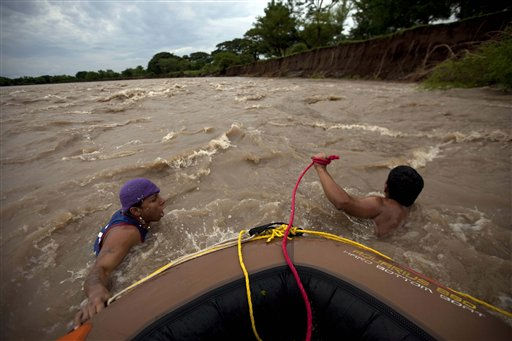 Junior Antonio Ramos, left, and Vladimir Antonio Ayala pull a boat being used to cross people back and forth &#34;La Paz&#34; river at the border between Guatemala and El Salvador after the bridge used to cross between the two countries collapsed due to  heavy rains in Santa Rosa, Guatemala, Thursday Oct. 13, 2011. Rains will likely continue during the next couple days as a low-pressure system hovers over southeastern Mexico, Guatemala and El Salvador, according to the National Hurricane Center in Miami, Florida. &#40;AP Photo&#47;Rodrigo Abd&#41; <span class=meta>(AP Photo&#47; Rodrigo Abd)</span>
