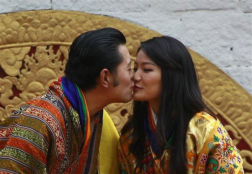Bhutan&#39;s King Jigme Khesar Namgyal Wangchuck, left, and Queen Jetsun Pema kiss in front of the crowd at the main stadium as part of their wedding celebrations in Thimphu, Bhutan, Saturday, Oct. 15, 2011. The 31 year-old reformist monarch of the small Himalayan Kingdom wed his commoner bride in a series of ceremonies at a 17th century monastic fortress Thursday. &#40;AP Photo&#47;Kevin Frayer&#41; <span class=meta>(AP Photo&#47; Kevin Frayer)</span>
