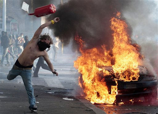 "<div class=""meta ""><span class=""caption-text "">A protestor hurls a canister clashes in Rome, Saturday, Oct. 15, 2011. Protesters smashed the windows of shops in Rome and torched a car as violence broke out during a demonstration in the Italian capital, part of worldwide protests against corporate greed and austerity measures.  (AP Photo/Gregorio Borgia) (AP Photo/ Gregorio Borgia)</span></div>"