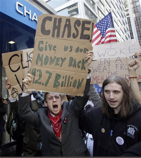 "<div class=""meta ""><span class=""caption-text "">Occupy Wall Street protesters march from their base in Zuccotti Park past several banks towards Washington Square Park before they head to Times Square for a rally Saturday, Oct.  15,  2011.   As many as 1,000 protesters were marching to a Chase bank branch in the financial district, banging drums, blowing horns and carrying signs decrying corporate greed. (AP Photo/David Karp) (AP Photo/ DAVID KARP)</span></div>"