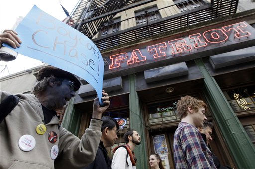 "<div class=""meta ""><span class=""caption-text "">A demonstrator affiliated with the Occupy Wall Street march through the streets of the Financial District, Saturday, Oct. 15, 2011 in New York.    As many as 1,000 protesters were marching to a Chase bank branch in the financial district, banging drums, blowing horns and carrying signs decrying corporate greed. (AP Photo/Mary Altaffer) (AP Photo/ Mary Altaffer)</span></div>"