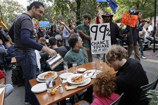 A demonstrator affiliated with the Occupy Wall Street march past a family dining at an outdoor restaurant, Saturday, Oct. 15, 2011 in New York.   As many as 1,000 protesters were marching to a Chase bank branch in the financial district, banging drums, blowing horns and carrying signs decrying corporate greed.   &#40;AP Photo&#47;Mary Altaffer&#41; <span class=meta>(AP Photo&#47; Mary Altaffer)</span>