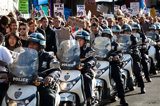 Police officers on scooters follow along a mass of Occupy Wall Street protestors as they march towards Times Square the day after successfully resisting a potential eviction from their camp in Zuccotti Park, Saturday, Oct. 15, 2011, in New York. As many as 1,000 protesters were marching Saturday morning to a Chase bank branch in the financial district, banging drums, blowing horns and carrying signs decrying corporate greed. Other demonstrations are planned around the city all day Saturday. &#40;AP Photo&#47;John Minchillo&#41; <span class=meta>(AP Photo&#47; John Minchillo)</span>