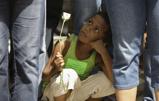 A Filipino street child holds a white rose as he participates in the observance of International Day of Overcoming Extreme Poverty at the Rizal Park in Manila, Philippines, Sunday, Oct. 16, 2011. The annual event also observed in other countries seeks to find ways of effectively easing poverty, which afflicts nearly a third of the Philippines&#39; 94 million people. &#40;AP Photo&#47;Aaron Favila&#41; <span class=meta>(AP Photo&#47; Aaron Favila)</span>