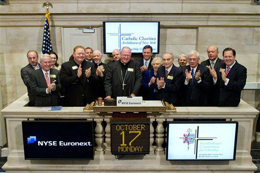In this photo provided by NYSE Euronext, Archbishop of New York Timothy M. Dolan, center, rings the opening bell at the New York Stock Exchange on Monday, Oct. 17, 2011 in New York.  A Catholic Charities press statement said Dolan met with &#34;corporate CEOs and guests of NYSE Euronext to discuss mutual responsibilities for building the common good and partnering with Catholic Charities.&#34; &#40;AP Photo&#47;NYSE Euronext, Ben Hider&#41; <span class=meta>(AP Photo&#47; Ben Hider)</span>