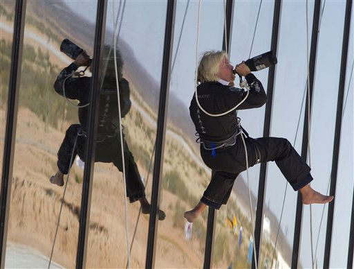 "<div class=""meta image-caption""><div class=""origin-logo origin-image ""><span></span></div><span class=""caption-text"">British billionaire Sir Richard Branson drinks champagne after repelling down the side of the new Spaceport America hangar Monday, Oct. 17, 2011 in Upham, N.M. Branson dedicated the newly completed terminal and hangar  on Monday, where his Virgin Galactic will stage its commercial space tourism venture. (AP Photo/Matt York) (AP Photo/ Matt York)</span></div>"