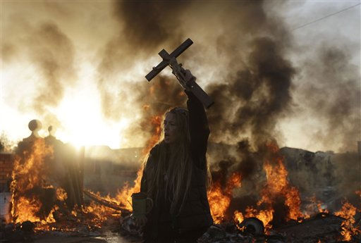 An Irish traveler resident holds up a cross for the media, in front of a burning barricade during evictions at the Dale Farm travellers site, near Basildon England, 30 miles &#40;50 kilometers&#41; east of London, Wednesday, Oct. 19, 2011.  Police in riot gear used sledgehammers to clear the way for the eviction of a community of Irish Travellers from a site where they have lived illegally for a decade.  A large force of police and bailiffs faced resistance from several dozen residents and supporters who threw bricks and struggled with officers.  &#40;AP Photo&#47;Matt Dunham&#41; <span class=meta>(AP Photo&#47; Matt Dunham)</span>