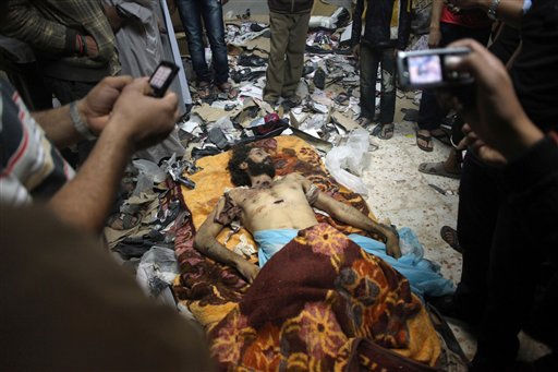 "<div class=""meta ""><span class=""caption-text "">People photograph a body revolutionary fighters claim to be that of Muatassim Gadhafi, son of Libyan dictator Moammar Gadhafi, in a house on the outskirts of Misrata, Libya, Thursday, Oct. 20, 2011. Moammar Gadhafi, Libya's dictator for 42 years until he was ousted in an uprising-turned-civil war, was killed Thursday as revolutionary fighters overwhelmed his hometown of Sirte and captured the last major bastion of resistance two months after his regime fell. Interim government officials said Muatassim also was killed in Sirte, and another, one-time heir apparent Seif al-Islam, was wounded and captured. (AP Photo/Manu Brabo) (AP Photo/ Manu Brabo)</span></div>"
