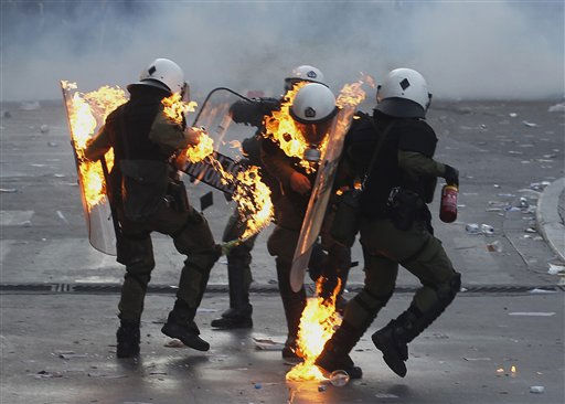 Riot policemen assist colleagues whose clothing caught fire after being hit by a petrol bomb during rioting in central Athens, Thursday, Oct. 20, 2011. A protester died and dozens were injured during an anti-austerity demonstration that turned violent in the Greek capital, hours before lawmakers were to vote on deeply unpopular new cutbacks demanded by creditors to keep Greece financial solvent.&#40;AP Photo&#47;Petros Giannakouris&#41; <span class=meta>(AP Photo&#47; Petros Giannakouris)</span>