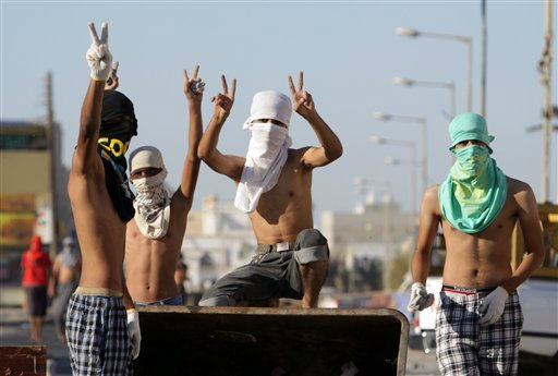 Anti-government protesters gesture in front of makeshift barricades Saturday, Oct. 22, 2011, in the western village of Dumistan, Bahrain. Protesters made a push Saturday to block roads and demonstrate nationwide. &#40;AP Photo&#47;Hasan Jamali&#41; <span class=meta>(AP Photo&#47; Hasan Jamali)</span>