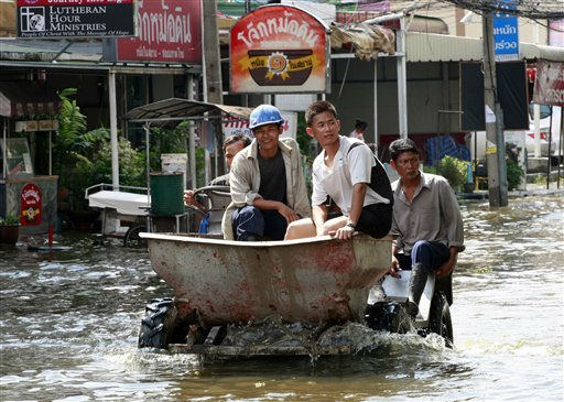 Workers ride on their vehicle through a flooded road in Bangkok, Thailand Saturday, Oct. 22, 2011. Thailand&#39;s catastrophic floods may take up to six weeks to recede, Prime Minister Yingluck Shinawatra said Saturday. Excessive monsoon rains have drowned a third of the Southeast Asian nation since late July, causing billions of dollars in damage and putting nearly 700,000 people temporarily out of work. &#40;AP Photo&#47;Apichart Weerawong&#41; <span class=meta>(AP Photo&#47; Apichart Weerawong)</span>